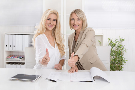 Two happy blond businesswoman working in a team recommend financial products. Stock Photo