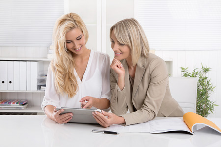 Two blond successful and attractive businesswoman working in a team analyzing business papers.