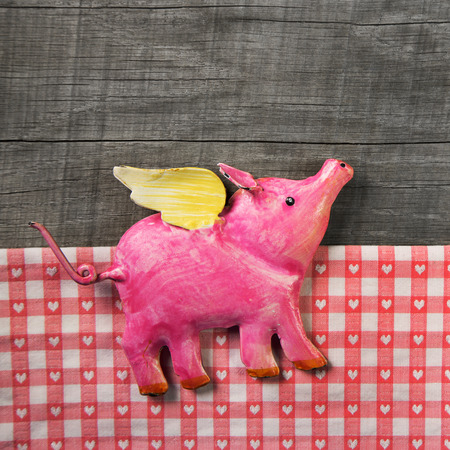 pig wings: Flying happy pink pig on wooden old checked background. Symbol for happiness and luck. Stock Photo