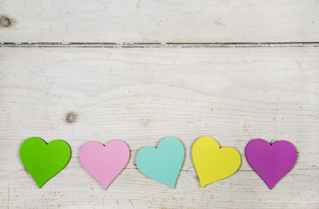 heartsickness: Colorful hearts in green, pink, yellow, rose and turquoise on old wooden shabby chic background for a greeting card.