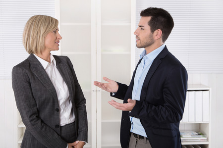 Two business people working in a team talking together in the office searching for solutions.