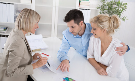 career counseling: Young married couple sitting with an adviser at desk in a guidance or professional business meeting planning their provision for ones old age.