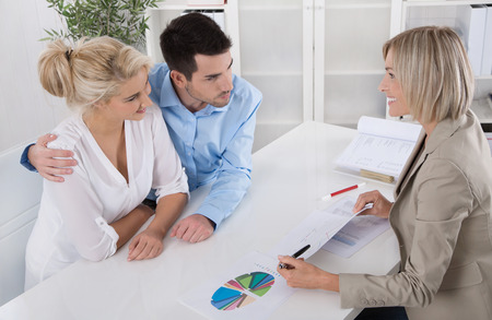 financial planning married: Young married couple sitting with an adviser at desk in a guidance or professional business meeting planning their provision for ones old age.