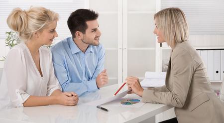 abastecimiento: Pareja casada joven que se sienta con un asesor en el escritorio en una orientaci�n o una reuni�n de negocios profesional la planificaci�n de su provisi�n para la vejez.
