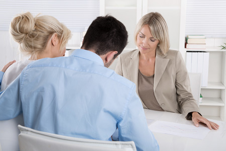 Young married couple sitting with an adviser at desk in a guidance or professional business meeting planning their provision for one's old age. Banque d'images