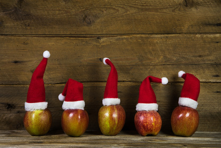 humorously: Decoration: Funny christmas greeting card with five red santa hats on apples with wooden background.
