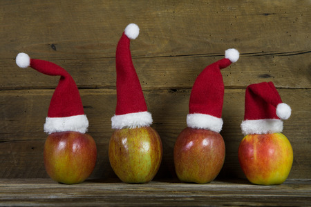 humorously: Decoration: Funny christmas greeting card with four red santa hats on apples with wooden background.