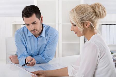 Deux hommes d'affaires assis dans le travail de bureau dans une équipe regardant bilan ou rapport d'évaluation.