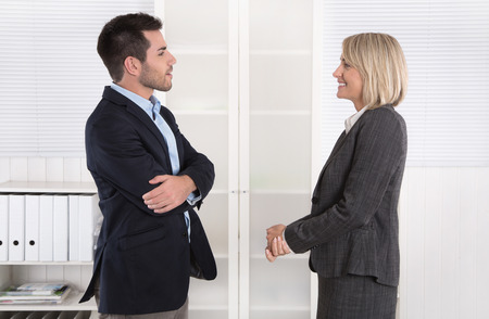 Business people in suit and dress talking together: small talk in a professional meeting. 免版税图像
