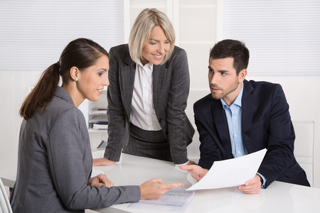 Business team of man and woman sitting around a table talking together in a meeting.