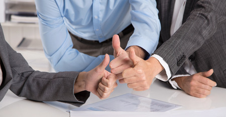 cooperative: Concept for successful teamwork or promise: business people making thumbs up gesture. Stock Photo