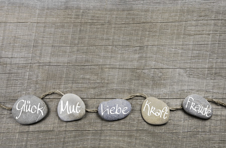 good wishes: Good wishes wooden background with stones and german text for luck, courage, love, power and happiness.