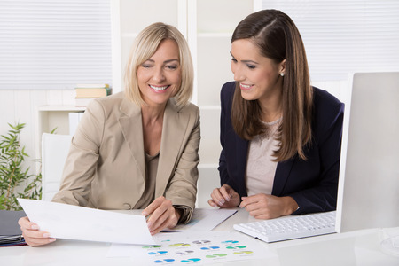 economists: Team of successful businesswoman analyzing together a financial report and statistics. Stock Photo