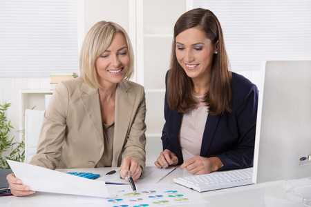 women talking: Team of successful businesswoman analyzing together a financial report and statistics. Stock Photo