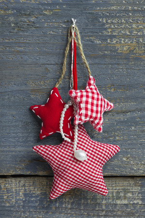 perls: Three red white checkered handmade stars hanging on a wall of wood for christmas decoration.
