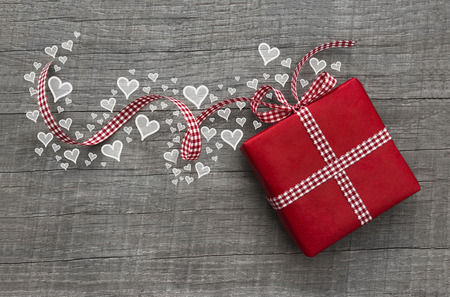 christmas promotion: Red valentines present with checked ribbon and hearts on grey wooden background for a gift certificate. Stock Photo