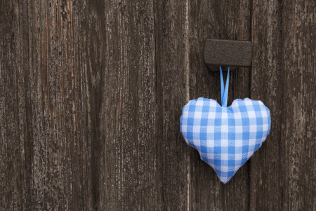 blue you: Fabric handmade blue and white checked heart in bavarian style hanging on an old wooden background.
