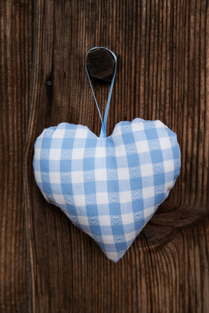 Fabric handmade blue and white checked heart in bavarian style hanging on an old wooden background. photo