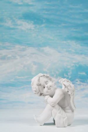 Dreaming or sad white angel on blue heaven background for a condolence or christening card. Stock Photo