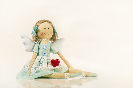 angel figurine: Angel figurine holding a red heart in her hands - isolated object for a greeting card.