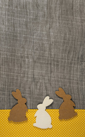 Easter greeting card with rabbits on the wooden frame in brown, yellow, grey and white. photo