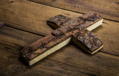 deceased: Old antique cross on wooden background for mourning or death concepts.
