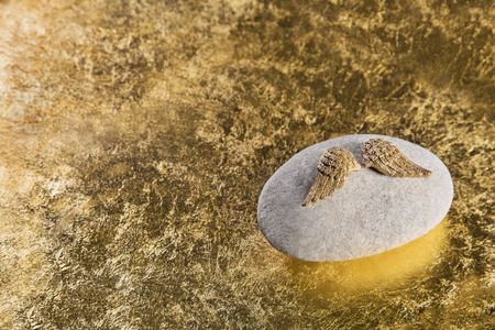 Golden angel wings on a stone for a death or sad background or for a condolence card. photo