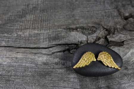funeral background: Golden angel wings on a black stone with grey old wooden background.