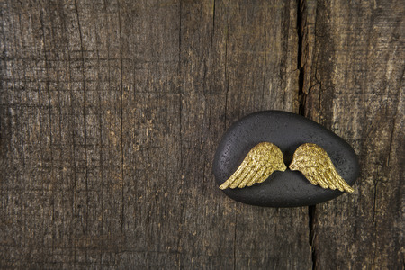announcing: Golden angel wings with a black stone on old wooden background for a card announcing somebodies death. Stock Photo