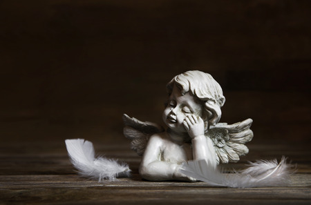 Sad angel with white feathers on a dark wooden background for bereavement.