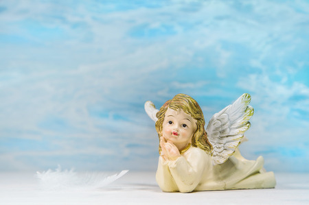 Dreaming angel on a blue heaven background: greeting card for death, christening or communion.