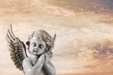 Sad praying angel on an orange mystic background for a condolence card. 스톡 콘텐츠
