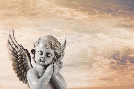 angel de la guarda: Ángel rezando triste en un fondo místico naranja para una tarjeta de condolencia. Foto de archivo