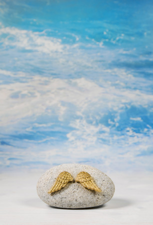 Golden angel wings with stone on blue heaven background for spiritual and condolence concepts. Stock Photo