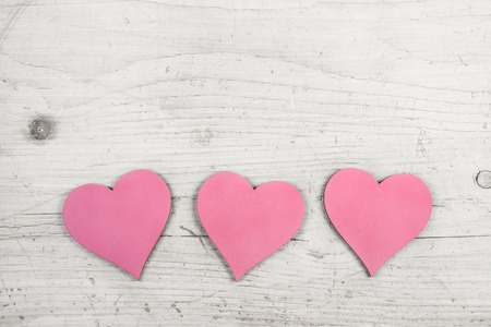three wishes: Three pink hearts on old wooden white shabby chic background for a greeting card.