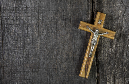 Jesus on cross: decoration on wooden background. Idea for a condolence or mourning card.