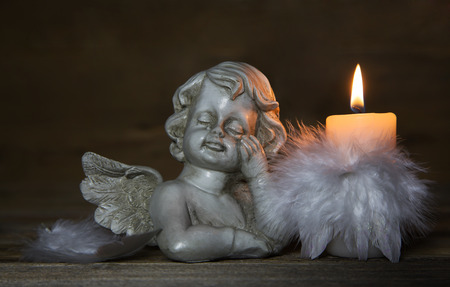 Sad crying angel with burning candle for bereavement or mourning background