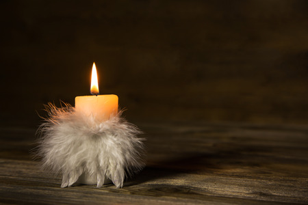 One burning candle with feathers on old wooden background. Idea for a condolence card. Stock Photo