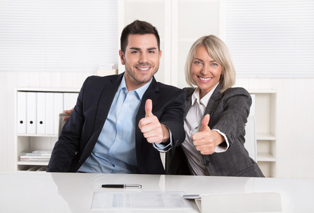 recommendation: Successful male and female business team or happy businesspeople making recommendation gesture. Stock Photo