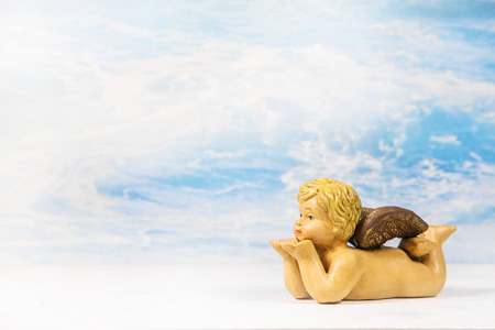 christening: Blowing angel figure on a heaven background. Idea for a greeting card. Stock Photo
