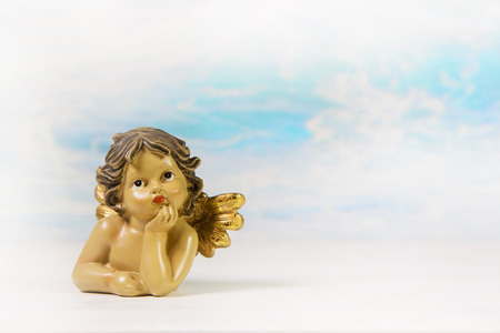 angel figurine: Dreaming guardian angel on a background.Idea for a greeting or congratulatory card.
