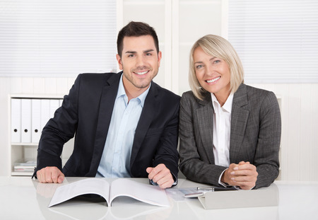 finance director: Smiling male and female business team sitting in the office. Successful collaboration or partnership,