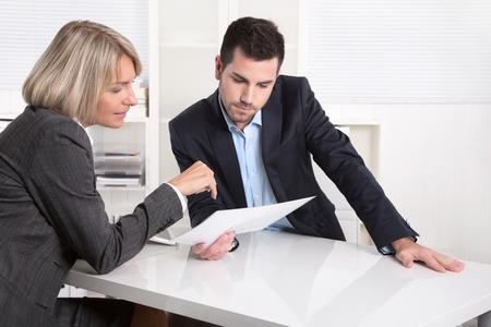 contratos: Equipo de negocios en una reuni�n mirando una hoja de papel