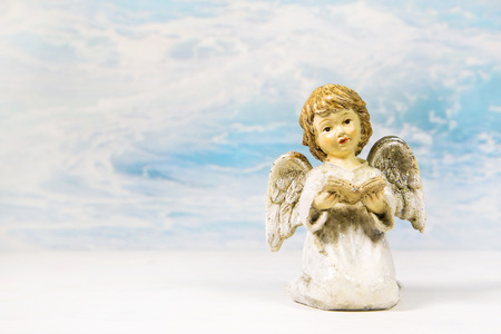 condolence: Christmas angel reading in a book telling a story on a background for a greeting card.