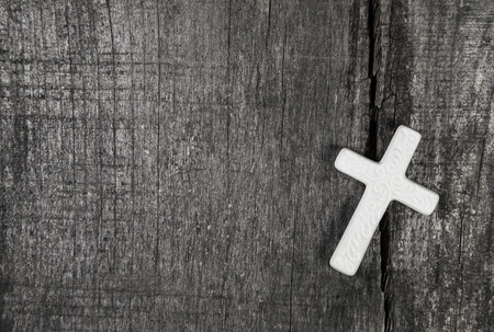 White cross on a gray wooden background. Idea for a condolence card.