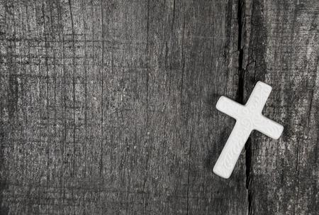 condolence: White cross on a gray wooden background. Idea for a condolence card.