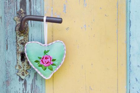 Coeur de tissu accroché à la main une poignée de porte ancienne. Banque d'images - 37790957