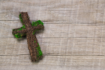 Condolence card: wooden handmade cross on a background.