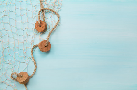 Maritime nautical blue and turquoise wooden background with a fishnet.
