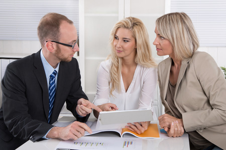 outgoings: Business team of man and woman sitting around a table in a meeting looking at tablet. Stock Photo
